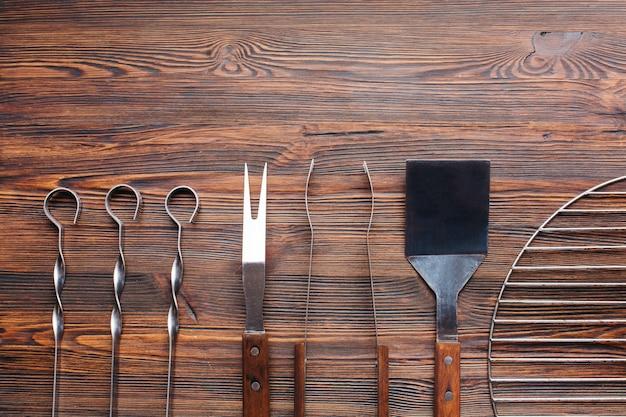 Linha de utensílios de churrasco na mesa de madeira