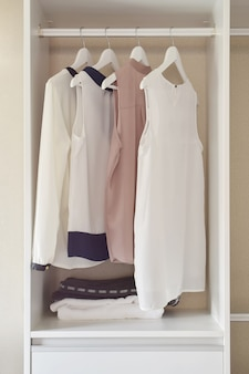 Linha de vestido pendurado no cabide no guarda-roupa branco