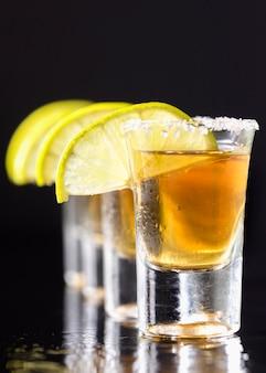 Linha de visão frontal de shots de tequila dourada com fatias de limão