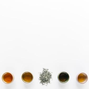 Linha de xícaras de ervas com folhas secas no fundo branco, com espaço de cópia