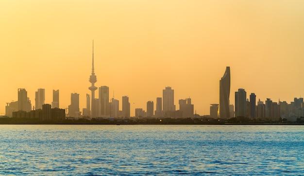 Linha do horizonte da cidade do kuwait ao pôr do sol