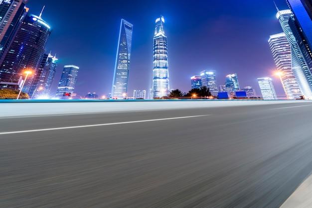 Linha do horizonte do pavimento asfáltico e cenário noturno da paisagem arquitetônica de xangai