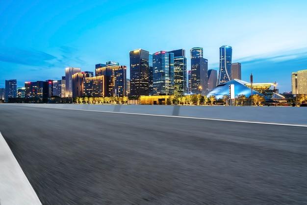 Linha do horizonte do pavimento asfáltico e paisagem noturna da paisagem arquitetônica moderna