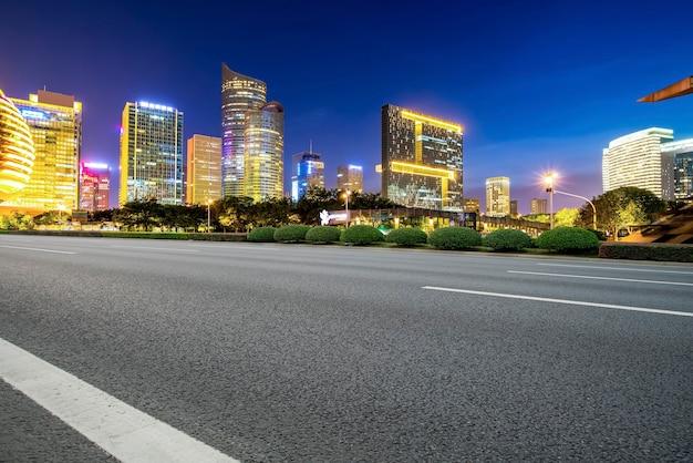 Linha do horizonte do pavimento da via expressa e cenário noturno da paisagem arquitetônica moderna