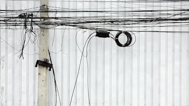 Linha elétrica do emaranhado no pólo na rua na cidade