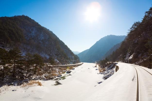 Linha ferroviária através da neve do inverno com luz solar