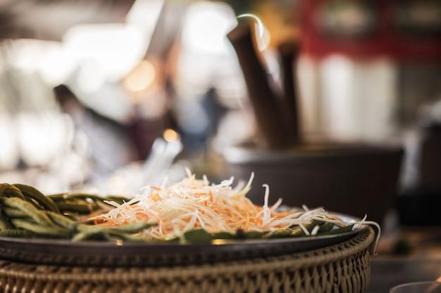 Linha papaia para os ingredientes da salada da papaia com almofariz do borrão. comida de rua na tailândia.