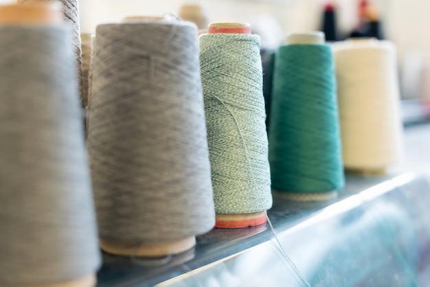 Linha recuada de lã de cashmere em carretéis cônicos em tons de verde, cinza e branco em uma fábrica de malhas com foco em um carretel de fio verde no centro