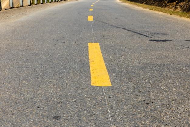 Linha tracejada amarela em estrada de asfalto, marcação de estrada