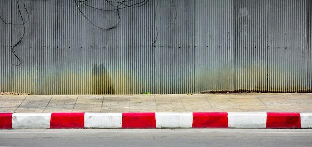 Linha vermelha e branca na estrada concreta no urbano.