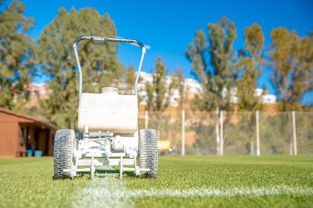 Linhas brancas desenhadas no campo de futebol com tinta branca na grama usando uma máquina especial antes de um jogo
