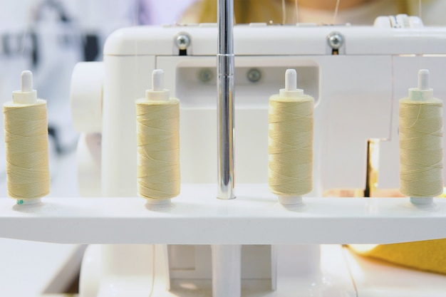 Linhas brancas e máquina de costura na mesa