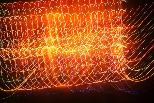 Linhas brilhantes multicoloridas onduladas contra um fundo escuro, tiro de longa exposição