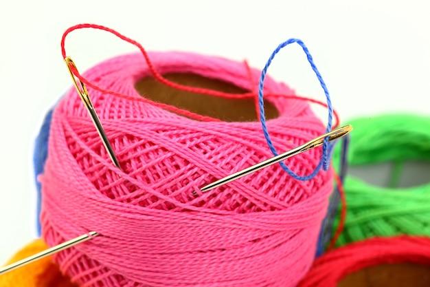 Linhas coloridas com agulhas para bordar, sobre um fundo branco