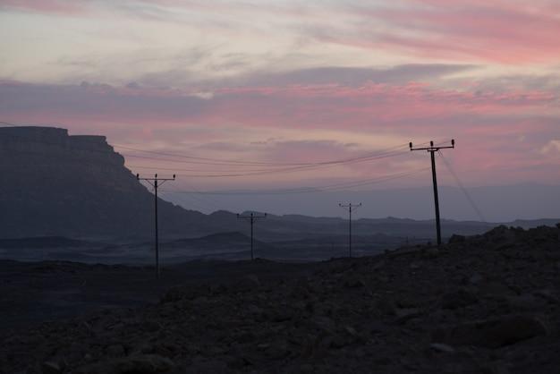Linhas de alta tensão no vale sob o céu nublado do pôr do sol