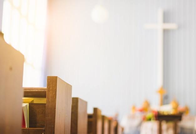 Linhas de banco de madeira vazio na igreja. foco seletivo, com fundo cruzado e gradiente
