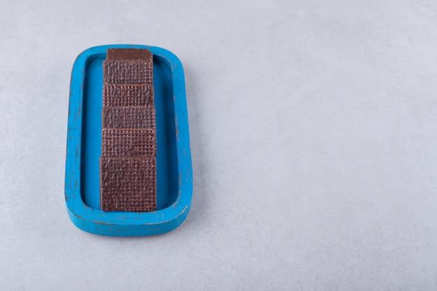 Linhas de bolachas revestidas de chocolate na placa de madeira na mesa de mármore.