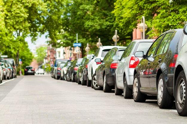 Linhas de carros estacionados na beira da estrada em bairro residencial