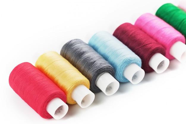 Linhas de costura artesanais de algodão colorido multicoloridas em uma fileira isoladas em um branco