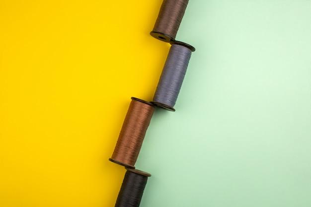 Linhas de costura coloridas em um fundo amarelo e verde