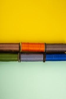 Linhas de costura coloridas em uma mesa verde-amarela