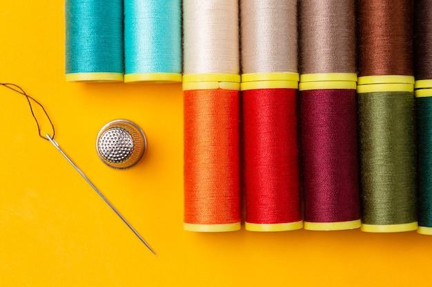 Linhas de costura de várias cores e dedal de agulha colocados ordenadamente