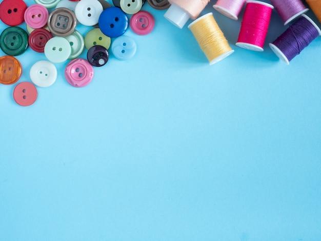 Linhas de costura multicoloridas e botões em fundo azul com cópia espaço plana leigos.