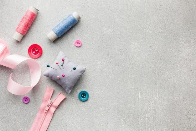 Linhas de costura multicoloridas e pequena almofada com agulhas