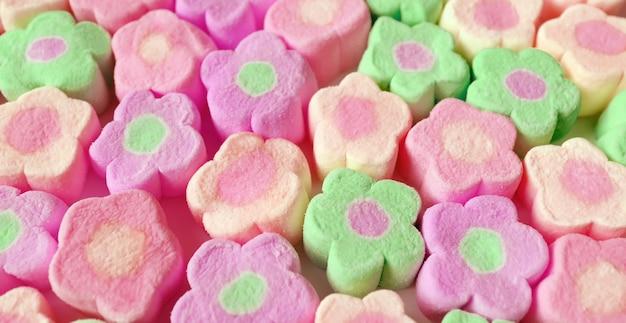 Linhas de doces de marshmallow em forma de flor rosa pastel e verde para fundo abstrato
