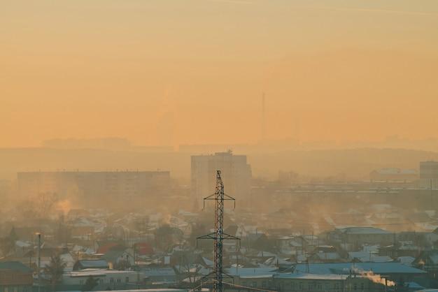 Linhas de energia na cidade ao amanhecer. silhuetas de edifícios urbanos entre poluição atmosférica no nascer do sol. cabos de alta tensão no céu amarelo laranja quente. indústria de energia ao pôr do sol. fonte de alimentação da cidade. meio urbano de névoa.