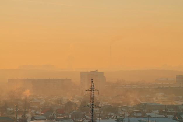 Linhas de energia na cidade ao amanhecer. silhuetas de edifícios urbanos entre poluição atmosférica no nascer do sol. cabos de alta tensão no céu amarelo laranja quente. indústria de energia ao pôr do sol. fonte de alimentação da cidade.