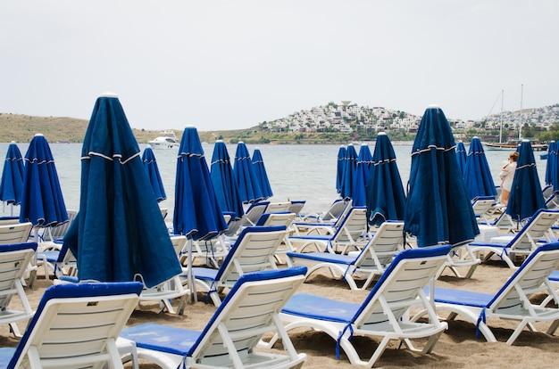 Linhas de espreguiçadeiras e guarda-sóis azuis vazios na praia. camel beach na turquia.