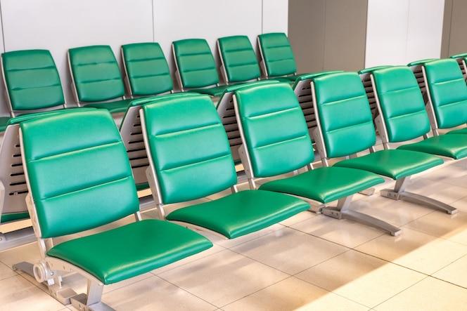 Linhas de modernas cadeiras verdes na sala de espera