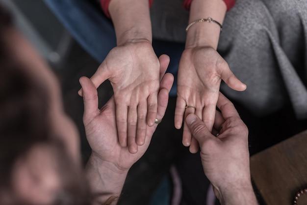 Linhas de palmeira. vista superior das palmas das mãos femininas nas mãos de quiromantes durante a sessão de leitura da sorte