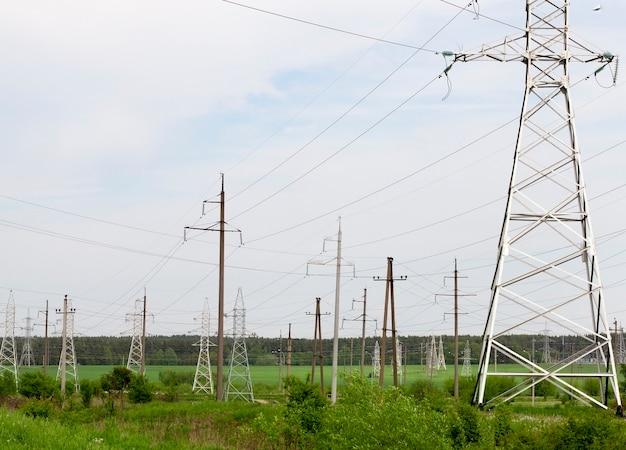 Linhas de transmissão de alta tensão de metal e concreto contra o céu