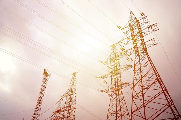 Linhas elétricas das torres de encontro a um fundo do céu nebuloso.