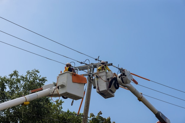 Linhas elétricas de energia apoiam os homens de serviço que trabalham para lidar com os danos após o furacão