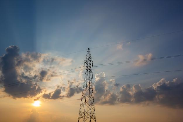 Linhas elétricas elétricas de alta tensão em pilões no por do sol.