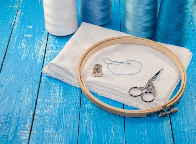 Linhas em bobinas com pano branco para o bordado e costura