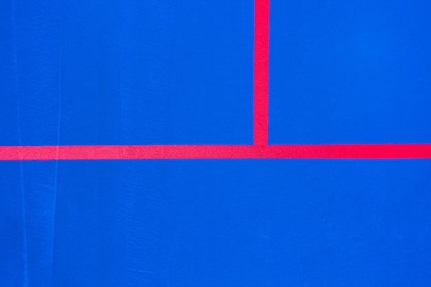 Linhas vermelhas que cruzam um assoalho pintado azul da cor intensa para usar-se como um fundo minimalista do projeto.
