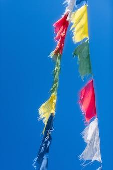 Linhas verticais de bandeiras coloridas de oração budista tibetana acenando eu