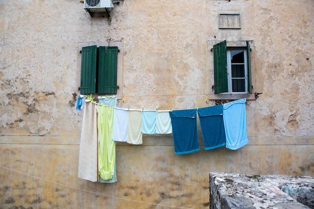 Linho multicolorido é seco do lado de fora da janela de uma casa velha