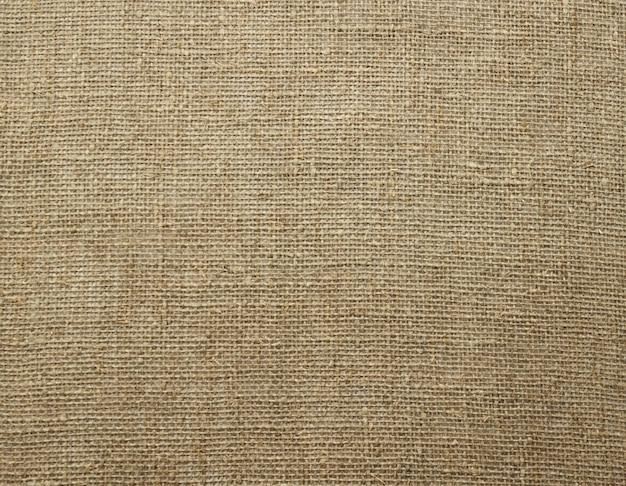 Linho natural de estopa de saco texturizado sem cor crua. textura de tecido de lona de saco de juta. fechar-se. foco seletivo suave. . espaço da cópia do texto.