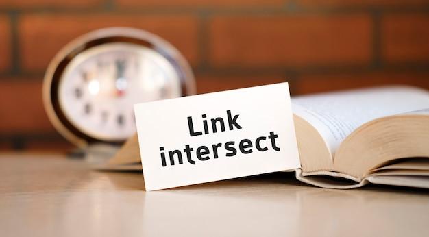 Link intersect - texto n folha branca com livro e relógio
