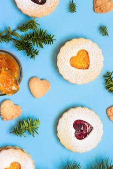 Linzer natal ou ano novo biscoitos cheios de geléia em fundo de papel azul.