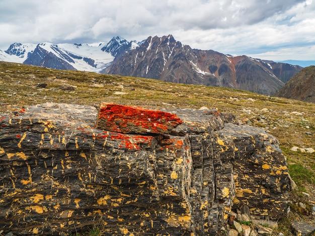 Líquen vermelho na pedra. líquen em uma pedra em close-up. pedra bruta multicolor na luz solar. textura natural com espaço de cópia. mineral incrível. pedaço de pedra.