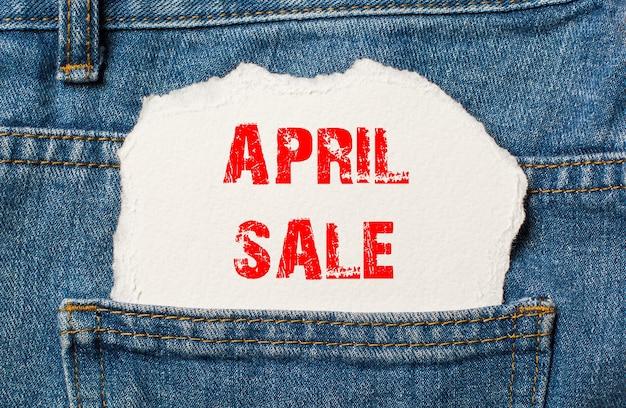 Liquidação de abril em papel branco no bolso da calça jeans azul