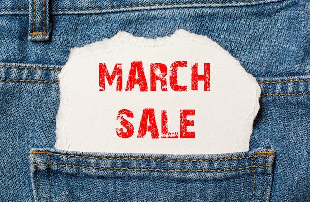 Liquidação de março em papel branco no bolso da calça jeans azul