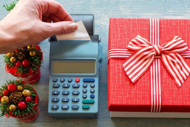 Liquidação de natal. mão segurando um cheque em branco em uma caixa registradora perto de uma caixa de presente vermelha com uma fita e pequenas árvores de natal com cones.