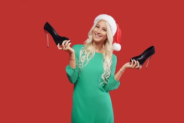 Liquidação de natal. mulher jovem e animada com chapéu de papai noel, vestido verde segurando sapatos pretos